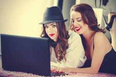 Achats en ligne d'amies sur l'ordinateur portable, se trouvant sur le tapis, vintage Image stock