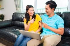 Achats en ligne de couples asiatiques avec la carte de crédit Image stock