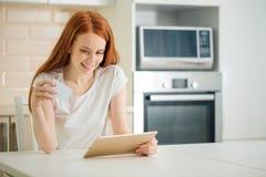 Achats en ligne de femme utilisant le comprimé et la carte de crédit dans la cuisine photographie stock
