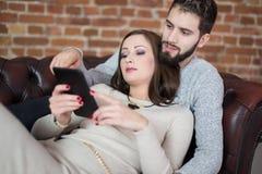 Achats en ligne de jeunes couples par le comprimé numérique sur le sofa Image libre de droits