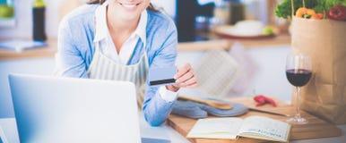 Achats en ligne de sourire de femme utilisant l'ordinateur et la carte de crédit dans la cuisine Images stock