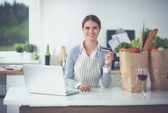 Achats en ligne de sourire de femme utilisant l'ordinateur et la carte de crédit dans la cuisine Photo libre de droits