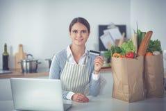 Achats en ligne de sourire de femme utilisant l'ordinateur et la carte de crédit dans la cuisine Photos stock