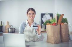 Achats en ligne de sourire de femme utilisant l'ordinateur et la carte de crédit dans la cuisine Photographie stock libre de droits