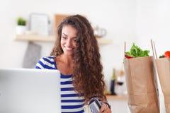 Achats en ligne de sourire de femme utilisant l'ordinateur et la carte de crédit dans la cuisine Image stock