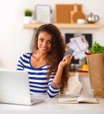 Achats en ligne de sourire de femme utilisant l'ordinateur et la carte de crédit dans la cuisine Photographie stock