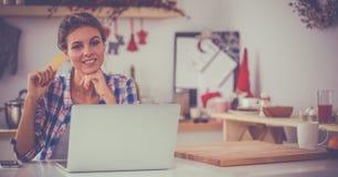 Achats en ligne de sourire de femme utilisant l'ordinateur et la carte de crédit dans la cuisine image libre de droits