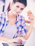 Achats en ligne de sourire de femme utilisant l'ordinateur et la carte de crédit dans la cuisine Femme de sourire photos stock