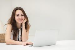 Achats en ligne Jeune et jolie fille s'asseyant à un ordinateur portable et à un m Images stock