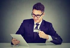 Achats et paiement en ligne Homme heureux payant avec la carte de crédit utilisant l'Internet de lecture rapide de comprimé images stock