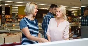Achats faisants blonds de jeune et d'une cinquantaine d'années femme dans un supermark Photographie stock