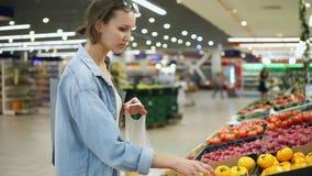 Achats Femme choisissant la bio tomate de jaune de nourriture dans le magasin ou le supermarché végétal Les prises un et le met d clips vidéos