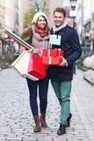 Achats heureux de couples pour Noël dans la ville Photos stock
