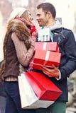 Achats heureux de couples pour Noël dans la ville Images stock