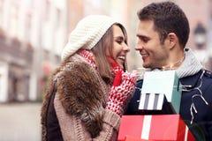 Achats heureux de couples pour Noël dans la ville Image libre de droits