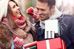 Achats heureux de couples pour Noël dans la ville Photo stock