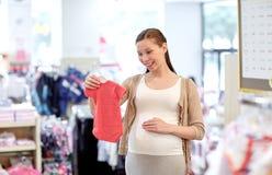 Achats heureux de femme enceinte au magasin d'habillement Photos libres de droits