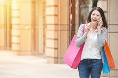 Achats heureux de femme parlant au téléphone portable Images stock