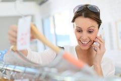 Achats heureux de jeune femme et parler au téléphone Image libre de droits