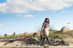 Achats heureux : Femme marchant sous le ciel bleu Photographie stock