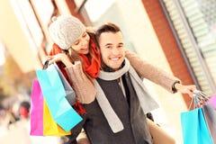 Achats joyeux de couples dans la ville Photo stock