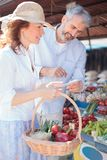 Achats mûrs heureux de couples pour des épiceries dans un marché organique local images stock