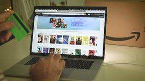 Achats principaux d'homme de jour d'Amazone Pays-Bas sur des affaires d'ordinateur portable banque de vidéos