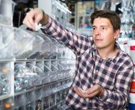 Acheteur adulte d'homme regardant des commutateurs pour la lumière et les prises dans le SH Photos stock