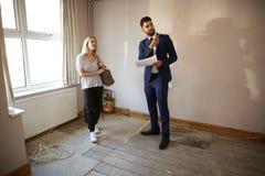 Acheteur féminin de première fois regardant l'enquête de Chambre avec l'agent immobilier photos libres de droits