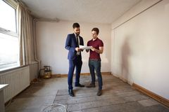Acheteur masculin de première fois regardant l'enquête de Chambre avec l'agent immobilier photos libres de droits