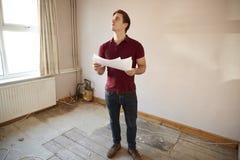 Acheteur masculin de première fois regardant l'enquête de Chambre dans la chambre d'être rénové photographie stock libre de droits