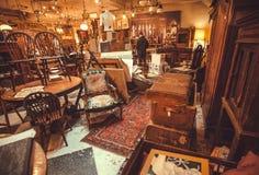 Acheteurs à l'intérieur du magasin d'antiquités avec des ustensiles, des lampes, des souvenirs et de rétros meubles Photographie stock libre de droits