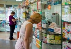 Acheteurs de vraies personnes se tenant à la fenêtre de la pharmacie d'Alushta images stock