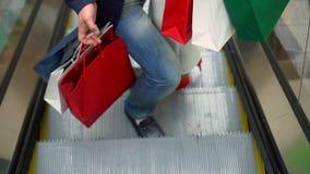 Acheteurs sur l'escalator au centre commercial avec des paquets des achats L'homme avec la montée de femme l'escalator avec clips vidéos