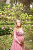 achic桃红色礼服的年轻未来母亲在开花的木兰附近站立 免版税库存照片