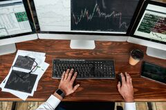 Achieve best. Top view of businessman, trader working, sitting by desk in front of multiple computer monitors. Stock