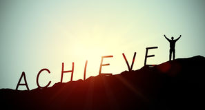 Achieve. Concept with words and a man cheering on the moutain Stock Image