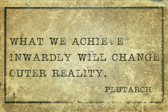 Achieve Plutarch. What we achieve inwardly - ancient Greek philosopher Plutarch quote printed on grunge vintage cardboard Stock Photos