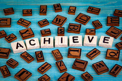 Achieve word written on wood block. Wooden alphabet on a blue background Stock Photography