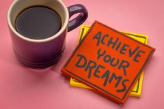 Achieve your dreams reminder note. Achieve your dreams reminder  handwriting on a sticky note wit a cup of coffee Stock Photography