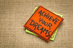 Achieve your dreams reminder note. Achieve your dreams reminder  handwriting on a sticky note against burlap canvas Royalty Free Stock Image