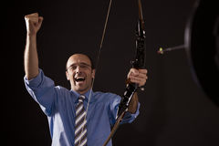 Achieved business goal. Handsome happy businessman cheering as he hit the target with bow and arrow symbolizing successful business Stock Images