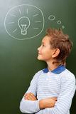 Achievement. Portrait of smart lad looking at blackboard with drawn lamp on it Stock Photography