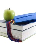 Achievement. Graduation cap, apple, and textbooks isolated on white Stock Photos