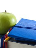 Achievement. Close up of a graduation cap, apple, and pencil on textbooks Stock Photo