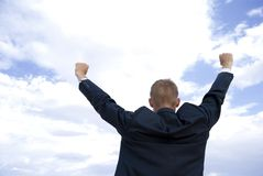 Achievement. Successful businessman or student in front of some clouds Royalty Free Stock Photos