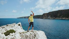 Achievement concept. Attractive man raising arm victoriously. Male tourist springing on top of the cliff and celebrating. Achievement concept. Attractive man stock video