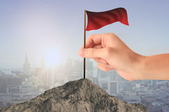 Achievement concept. Hand placing waving red flag on mountain top. City background. Achievement concept Stock Images