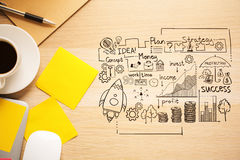 Achievement concept. Top view of light wooden desktop with coffee cup, yellow stickers, other items and business sketch. Achievement concept Stock Photo