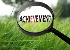 Achievement. Magnifying glass with the word achievement on grass background. Selective focus stock images